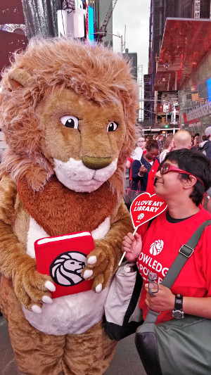 Leonard in a lion outfit and Sumana in street clothes, facing each other among the crowds of Times Square.