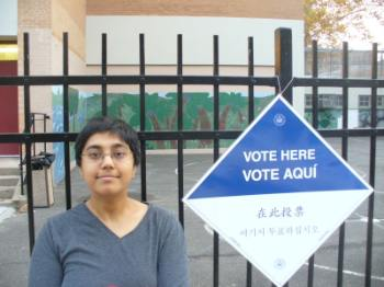 Sumana near a polling place sign